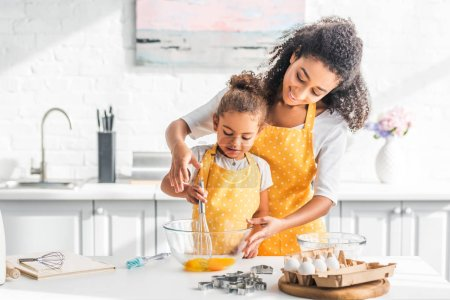 Photo for Smiling african american mother helping daughter mixing eggs for dough in kitchen - Royalty Free Image