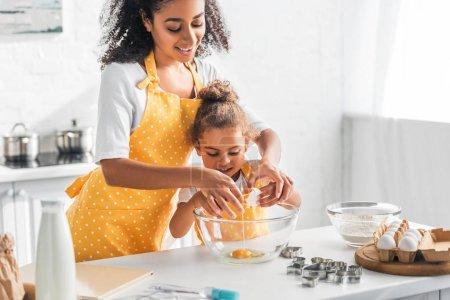smiling african american mother helping daughter breaking egg for preparing dessert in kitchen
