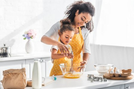 Photo for African american mother helping daughter whisking eggs for dough in kitchen - Royalty Free Image