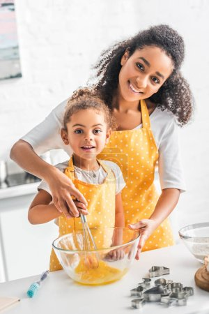 smiling african american mother helping daughter whisking eggs for dough in kitchen, looking at camera