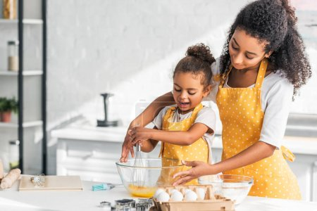 african american mother and daughter in yellow aprons whisking eggs for dough in kitchen
