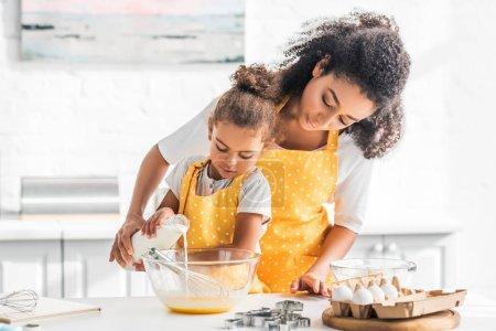 Photo pour Afro-américaine mère et fille préparant la pâte et verser le lait dans un bol dans la cuisine - image libre de droit