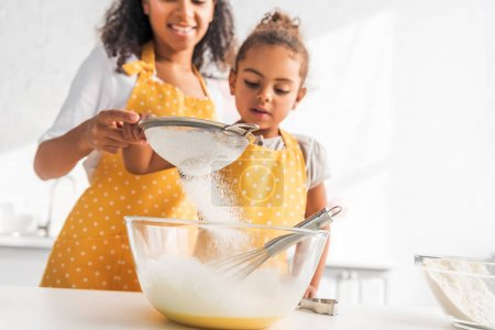 Photo for Cropped image of african american mother and daughter preparing dough and sieving flour in kitchen - Royalty Free Image