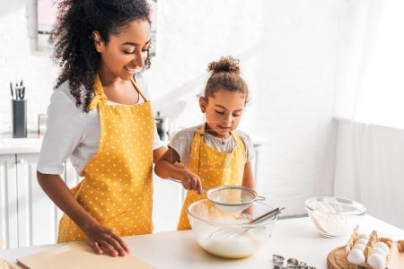 Photo for Cheerful african american mother and daughter preparing dough and sieving flour in kitchen - Royalty Free Image