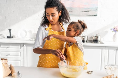 Photo for African american daughter preparing and whisking dough, pointing on something to mother in kitchen - Royalty Free Image