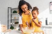 """Постер, картина, фотообои """"афро-американских дочь подготовка и взбивать тесто в кухне"""""""