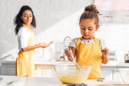 Photo for Selective focus of african american daughter preparing and whisking dough in kitchen - Royalty Free Image
