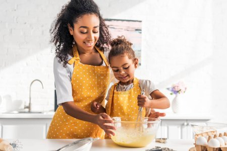 smiling african american mother helping daughter preparing and whisking dough in kitchen