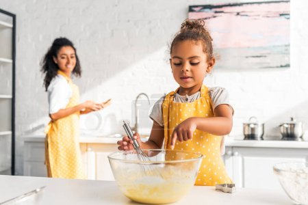 african american daughter preparing and whisking dough, putting finger into bowl in kitchen