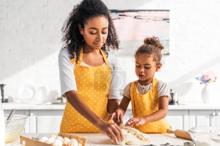 Photo for African american mother and daughter kneading dough in kitchen - Royalty Free Image