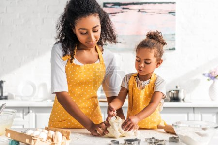 Photo for African american mother and daughter kneading dough together in kitchen - Royalty Free Image