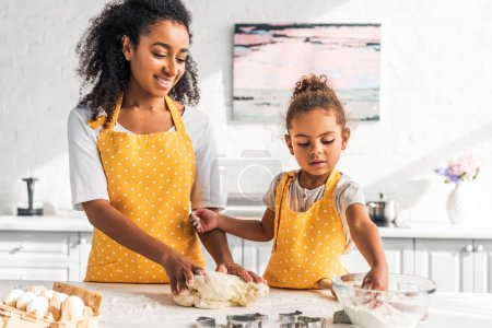 Photo for Smiling african american mother and daughter kneading dough for dessert in kitchen - Royalty Free Image
