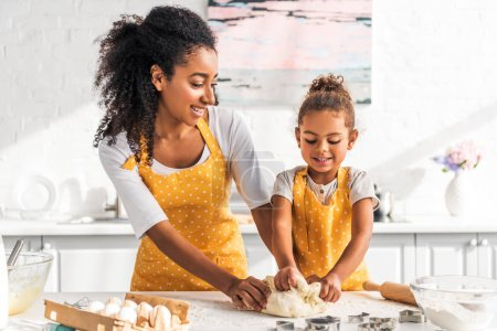 cheerful african american mother and daughter kneading dough in kitchen