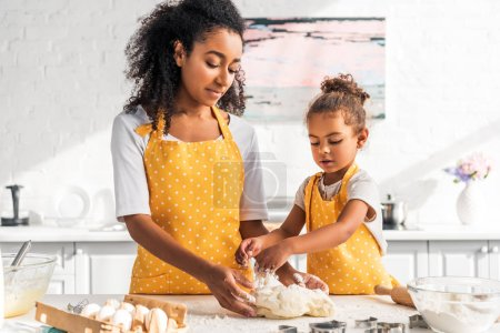 african american mother and daughter in aprons kneading dough with hands in kitchen