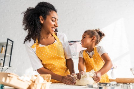 low angle view of smiling african american mother and daughter kneading dough and looking at each other in kitchen