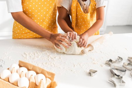 Photo for Cropped image of african american mother and daughter kneading dough in kitchen - Royalty Free Image