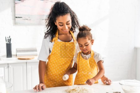 Photo for African american mother and daughter rolling dough with rolling pin in kitchen - Royalty Free Image
