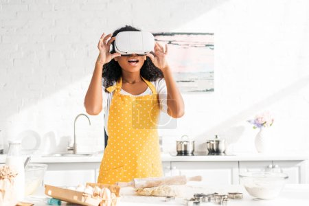 shocked african american girl in apron touching virtual reality headset at table with dough in kitchen