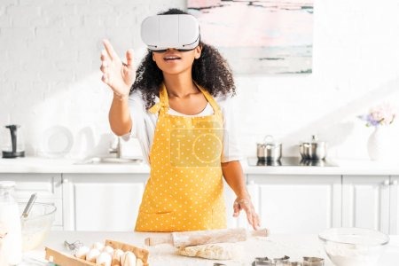excited african american girl in apron and virtual reality headset reaching hand at table with dough in kitchen
