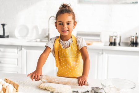 smiling adorable african american kid rolling dough with rolling pin in kitchen