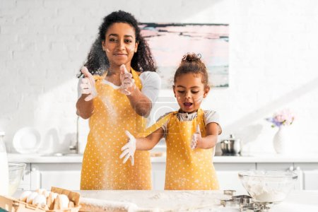 african american mother and daughter preparing dough and having fun with flour in kitchen