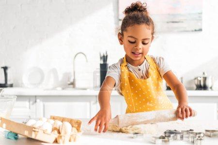Photo pour Adorable enfant afro-américain, rouler la pâte avec le rouleau à pâtisserie en cuisine - image libre de droit