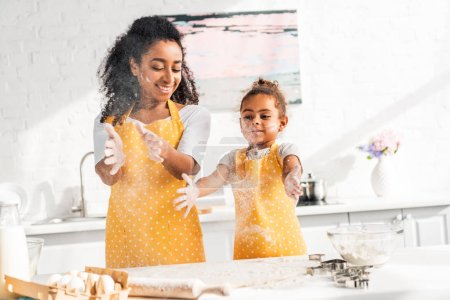 Photo for Cheerful african american mother and daughter preparing dough and having fun with flour in kitchen - Royalty Free Image