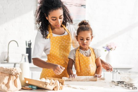 african american mother looking at daughter rolling dough with rolling pin in kitchen