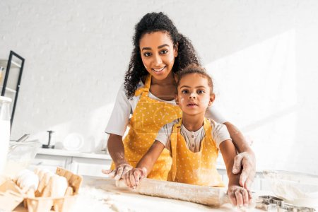 african american mother helping daughter rolling dough with rolling pin in kitchen and looking at camera