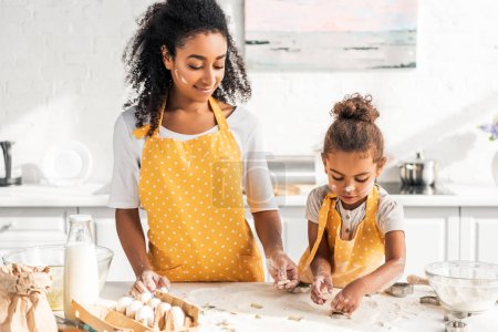 african american mother and daughter preparing cookies with molds at home