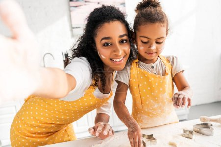 camera point of view of smiling african american mother and daughter preparing cookies with molds in kitchen
