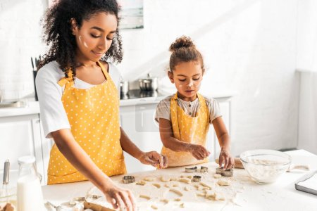 african american mother and daughter preparing cookies with molds together in kitchen