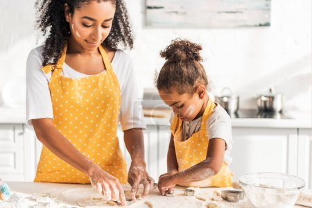 african american mother and adorable daughter preparing cookies with molds in kitchen