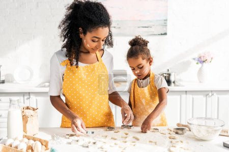 Photo for African american mother and daughter in yellow aprons preparing cookies with molds in kitchen - Royalty Free Image