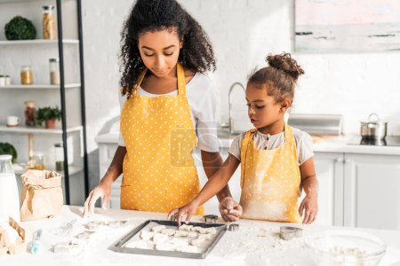 african american mother and daughter in yellow aprons looking at cookies on tray in kitchen
