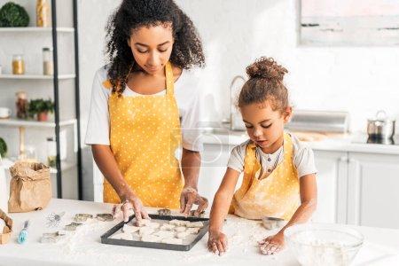 Photo pour Afro-américaine mère et fille prépare des cookies et de les mettre sur le plateau dans la cuisine - image libre de droit
