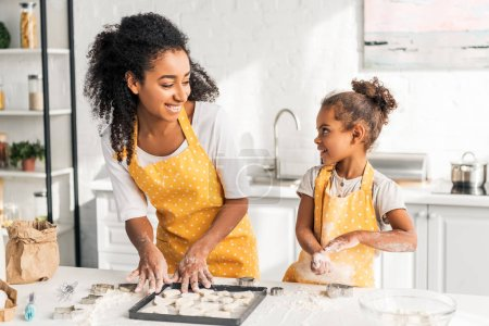 smiling african american mother and daughter preparing cookies and looking at each other in kitchen