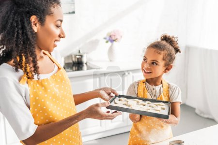 african american mother and daughter holding tray with unbaked cookies in kitchen and looking at each other