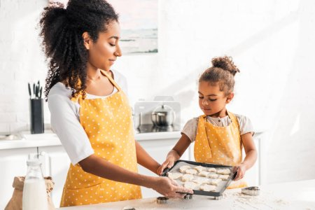 african american mother and daughter in aprons holding tray with unbaked cookies in kitchen
