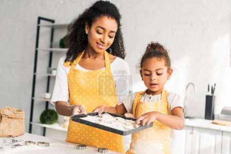 cheerful african american mother and daughter holding tray with unbaked cookies in kitchen