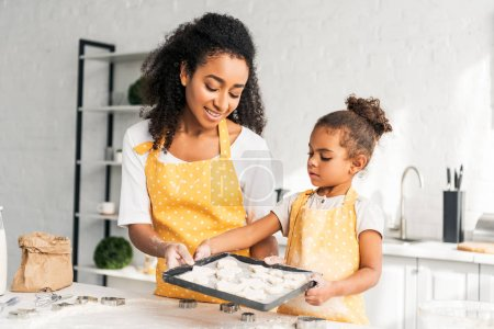 african american mother and daughter holding tray with unbaked cookies together in kitchen