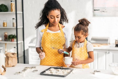 Photo for African american mother and daughter applying oil on unbaked cookies in kitchen - Royalty Free Image