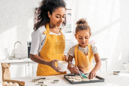 african american mother and daughter in yellow aprons applying oil on unbaked cookies in kitchen