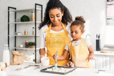 smiling african american mother and daughter applying oil on unbaked cookies in kitchen