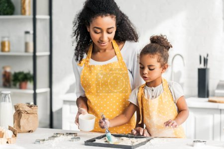 attractive african american mother and adorable daughter applying oil on unbaked cookies in kitchen