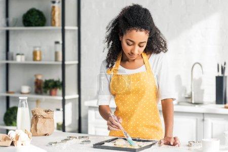 Photo pour Attrayant afro-américain fille dans tablier appliquer de l'huile sur les biscuits non cuits dans la cuisine - image libre de droit