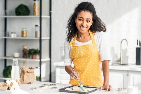 Photo for Beautiful smiling african american girl in apron applying oil on unbaked cookies in kitchen and looking at camera - Royalty Free Image