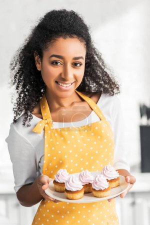 Photo for Portrait of smiling attractive african american girl in apron holding homemade cupcakes and looking at camera in kitchen - Royalty Free Image