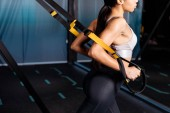 Cropped view of sportive girl working out with suspension straps in sports gym