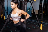 Beautiful sportive girl exercising with suspension straps in sports gym